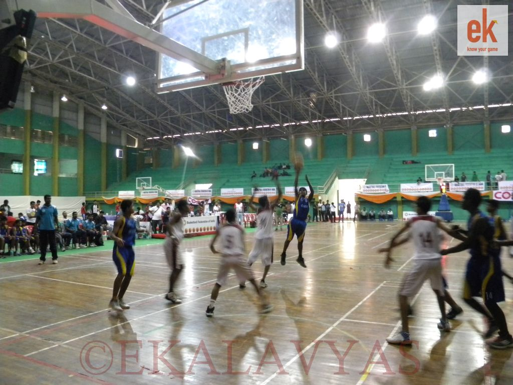 Tamil Nadu player (in blue) with a jumper in the paint against Rajasthan (in white).